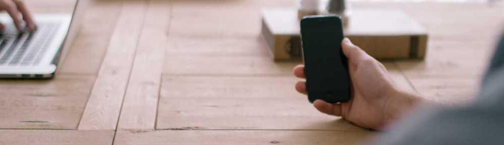 Bilde av et bord, en laptop og en hånd som holder en mobiltelefon